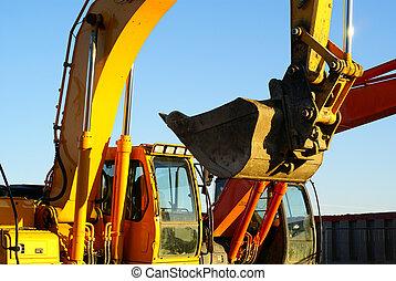 Hydraulic excavator at work. Shovel bucket against blue sky