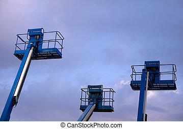 Hydraulic Lift - Three hydraulic lifts against a morning...