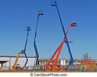 hydraulic lifts - cherry pickers and fork lifts in a rental yard
