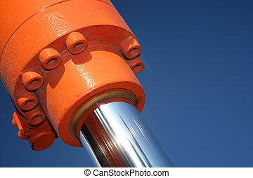 A close up of a hydraulic ram against a blue sky.