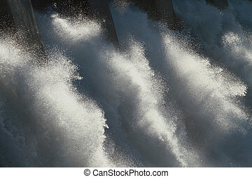 The sun dramatically backlighting the spillway of a large hydroelectric dam overflow.
