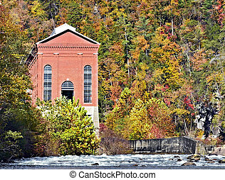 A tall brick building part of a power plant on a lake in the fall.