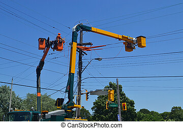 Hydro workers on a lift truck repairing hydro lines in Hamilton Ontario, under blue sky.