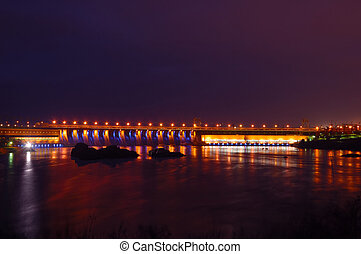 Hydroelectric dam in the night with colored lights,...