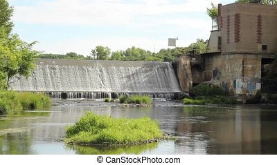 hydroelectric dam - water flowing over a small hydroelectric...