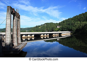 A hydroelectric barrage on the Dordogne river near Argentat, Correze, France, forms a perfect mirror image in the morning sun.