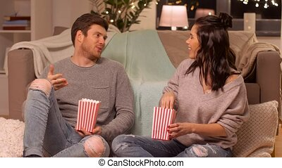 happy couple eating pop corn at home