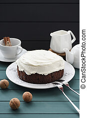 Hygge style dessert. Chocolate cake with cream cheese, black tea and walnuts on dark background