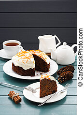 Hygge tea party. Black tea and traditional fruit cake with cream icing and orange peel on blue background