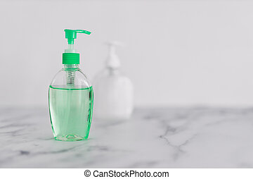hygiene and protecting from viruses and bacteria, hand sanitizer and liquid soap bottle on marble bathroom