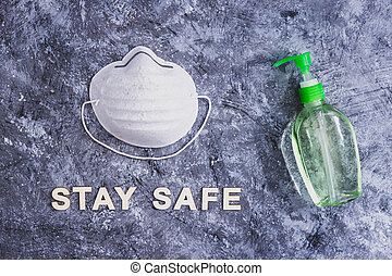 hygiene against viruses outbreak like covid-19 and other bacteria, hand sanitizer and face mask side by side with stay safe message