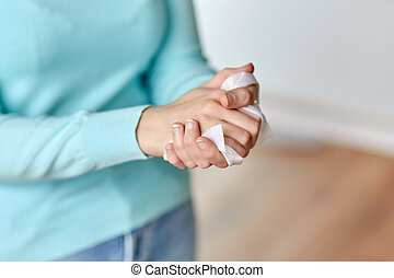 woman cleaning hands with antiseptic wet wipe