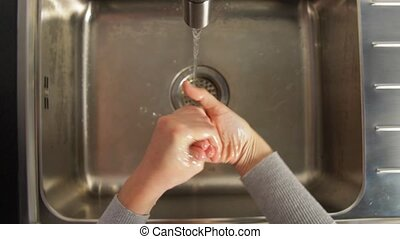 woman washing hands with liquid soap in kitchen - hygiene, ...