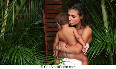 Hygiene - Pretty mother in towel holding her naked baby in...