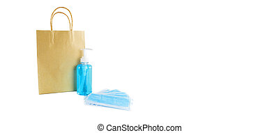 Hygienic masks , alcohol gel and paper bag on white background. Medical face mask, alcohol sanitizer in pump head bottle  on white background with copy space banner.