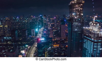 Hyper Lapse Motion Time Lapse at Night above of modern city center with skyscrapers and busy car traffic in futuristic modern Jakarta, Indonesia, Aerial Drone hyperlapse Establishing Shot