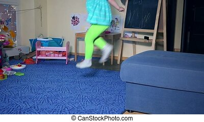 Hyperactive little child boy climb on sofa and jump down at home