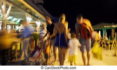 Hyperlapse of family walking along street at night