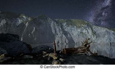 hyperlapse of night starry sky with mountain and ocean beach...