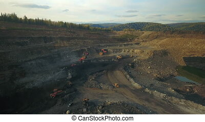 Hyperlapse panorama of coal mining quarries, red excavators dig coal and load into yellow dump trucks