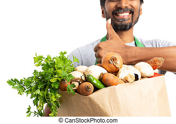 Hypermarket employee holding bag of vegetables showing thumb...