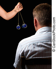 Hypnosis - Woman hypnotizes man with a swinging watch during...