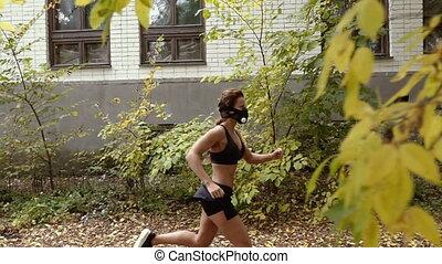 Hypoxic mask. Athletic girl runs in a hypoxic mask.
