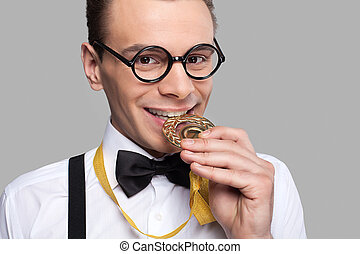 I am a winner! Cheerful young man in bow tie holding a gold medal and biting it while standing against grey background