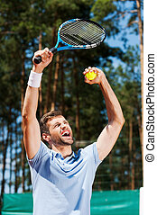 I am a winner! Happy young man in polo shirt raising his tennis racket up while standing on tennis court