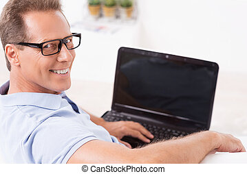 I am always online. Top view of cheerful mature man working on laptop and looking over shoulder while sitting on the couch at home