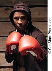 I am ready to fight. Confident young African man in hooded shirt and boxing gloves looking at camera while standing against wooden background