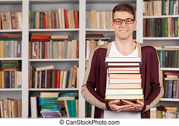 I am ready to my final exam. Cheerful young man holding a book stack and smiling while standing at the library