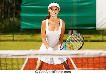 I am ready to play! Beautiful young woman in sports clothing playing tennis while standing on court