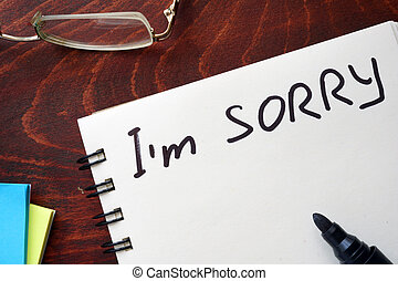 I am sorry written on notepad on a table.