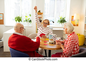 Delighted senior woman holding her hand up