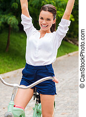 i, amor, riding!, feliz, mulher jovem, montando, dela, bicicleta, e, mantendo, braços levantaram