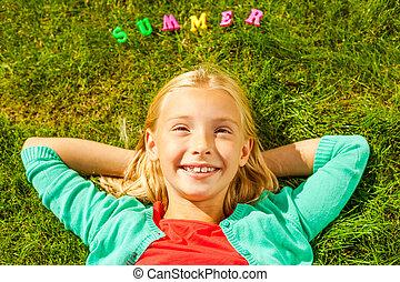 i, amor, summer!, vista superior, de, cute, menininha, segurar passa, atrás de, cabeça, sorrindo, enquanto, mentindo, ligado, a, grama verde, com, plástico, coloridos, letras, deitando, sobre, dela, cabeça
