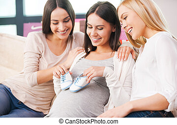 I believe he will love them. Happy young pregnant woman holding baby booties on her abdomen and smiling while two friends sitting close to her on the couch