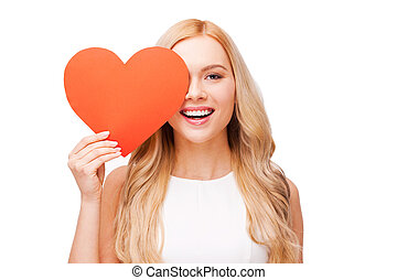 I believe in love! Beautiful young blond hair woman holding heart shaped valentine card in front of her eye and smiling while standing isolated on white