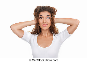 I can?t hear anything. Beautiful young women standing with her hands closing ears while isolated on white
