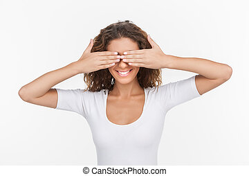 I can?t see anything. Beautiful young women standing with her hands closing eyes while isolated on white