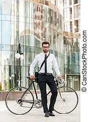 I choose the green way! Full length of handsome young businessman leaning at his bicycle and looking at camera while standing outdoors