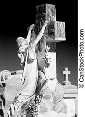 Cemetery scene with a statue of a woman clinging to a cross in a posture of grief or hope with another cross from another tomb far in the background.