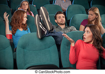 I don?t care about anyone. Young men holding his feet on the seat while watching movie at the cinema