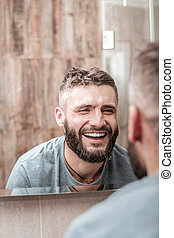 Joyful positive man smiling to his reflection