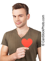 I guess I am in love. Handsome young man holding a paper heart and smiling while standing isolated on white background