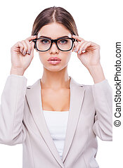 I have my own vision of business. Confident young businesswoman adjusting her glasses while standing against white background