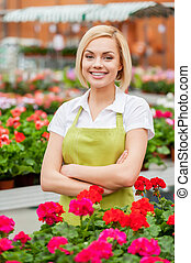 I have the best job in the world! Attractive young blond hair woman in apron keeping arms crossed and smiling while standing in a greenhouse with flowers all around her