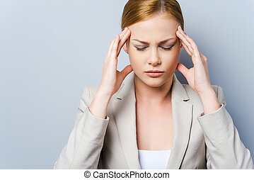 I have to concentrate. Depressed young businesswoman touching her cheekbone and keeping eyes closed while standing against grey background