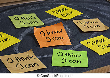 I know I can - self confidence and motivational concept, color sticky notes on blackboard with white chalk smudges, focus on central orange, note